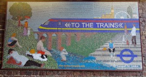 In a tunnel leading to Waterloo Station one of series of large mosaic panels shows a training speeding over an aqueduct, like the one on the ICI door. The summer scene of people sitting on the hillside and enjoying the water is inspired by the art of Georges Seurat.